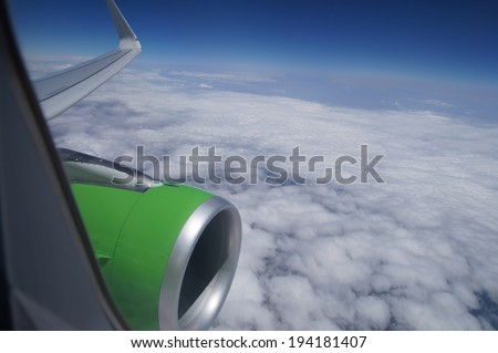 View from airplane window with blue sky and white clouds with room for text  - stock photo