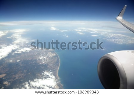 View from an aeroplane window of sea and coast - stock photo