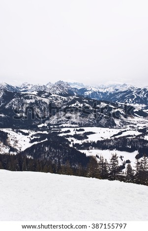 View from atop ski hill under cloudy skies above wide snow covered mountain range and scattered scenic forests - stock photo