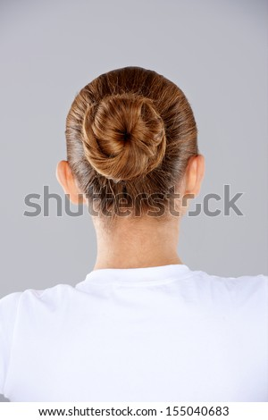 View from behind a woman with her brunette hair done in a neat bun on the back of her head against a grey studio background - stock photo
