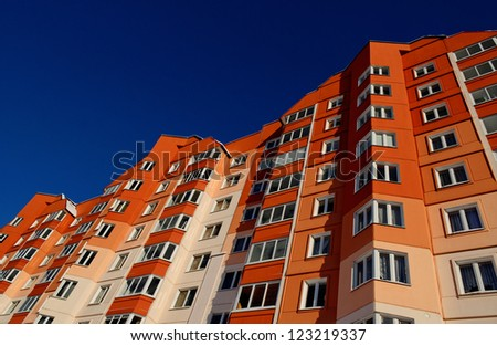 view from below at red apartment building - stock photo