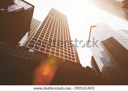 View from below of a high-rise buildings with contemporary architecture in business center in day. Tall modern skyscrapers against grey sky in big city - stock photo