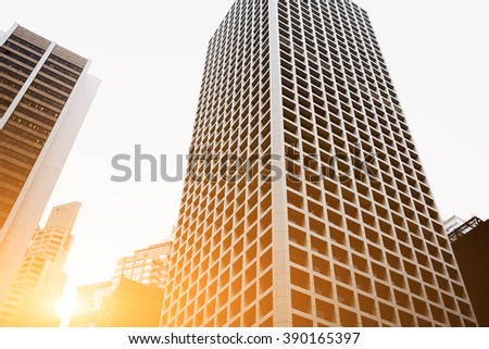 View from below of a tall modern skyscrapers in big metropolitan city against grey sky. High-rise buildings with new contemporary architecture in business center - stock photo