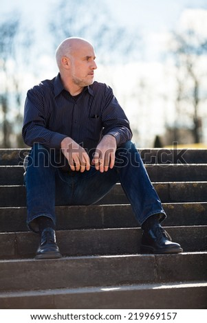 View from below of a thoughtful middle-aged man sitting on a flight of steps staring into the distance with a serious expression against a blue sky - stock photo