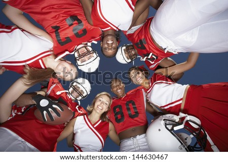 View from below of football players and cheerleaders in huddle against clear sky - stock photo