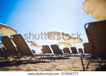 View from below of free deck chairs and sun umbrellas on a beach in sunny summer day against blue sky background with copy space area for your text message or advertising content, vacations and rest - stock photo