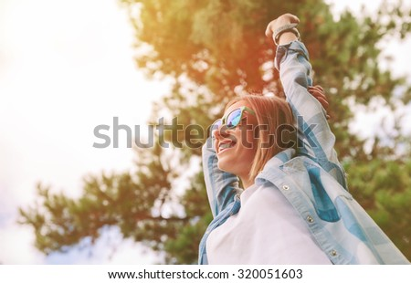 View from below of young beautiful happy woman with sunglasses and blue plaid shirt raising her arms over a sky and trees background. Freedom and enjoy concept. - stock photo