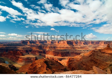 View from Dead Horse Point of the Colorado River with blue sky and clouds - stock photo