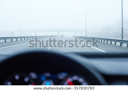 view from luxury modern car inside with part of interior, lighted dashboard and indicators on heavy foggy empty straight road during very cloudy day and rain - stock photo