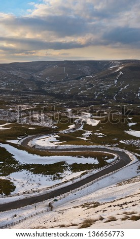 View from Mam Tor hill / Mountain, Peak District National Park along winding road in winter snow - stock photo