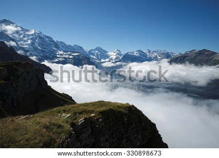 View from Mannlichen at the Bernese Alps (Berner Oberland, Switzerland). The Mannlichen is a mountain (2,343 metre) in the Swiss Alps within the Canton of Bern. Reachable from Wengen or Grindelwald. - stock photo