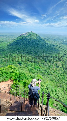 View from mount Sigiriya, Sri Lanka (Ceylon) with tourist on shot. Sigiriya ( Lion's rock ) is a large stone and ancient palace ruin in the central  Sri Lanka - stock photo