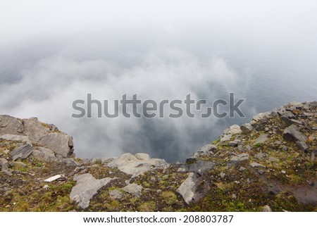 View from Nordkapp with mountain and mist - stock photo