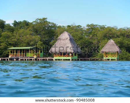 View from sea surface of tropical bungalows over water with lush vegetation, Caribbean, Bocas del Toro, Panama - stock photo