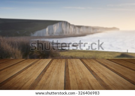 View from Seaford Head towards Seven Sisters at sunrise with wooden planks floor - stock photo
