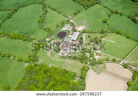 View from the air of a farm and allotments near the village of Capel in Surrey in the English countryside on a sunny Spring day. - stock photo