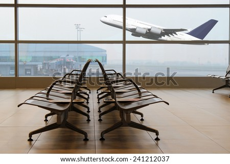 View from the airport terminal to a departing plane - stock photo