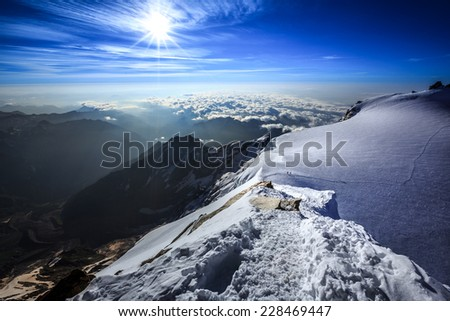View from the Alpine summit towards glacier and valley, background with cloudy sky and sun. - stock photo