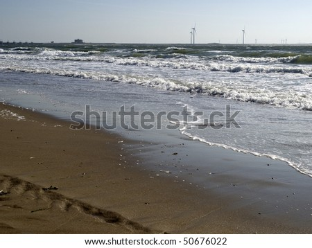 View from the beach on storm surge barrier the Neeltje Jans and on windmills on the dam - stock photo