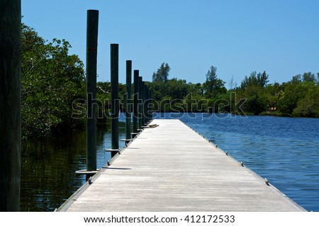 View from the beginning of a long pier or boat dock  on Imperial River in Bonita Springs, Florida. - stock photo