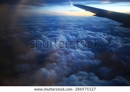 view from the bird's-eye view of the airplane window at the horizon and clouds - stock photo