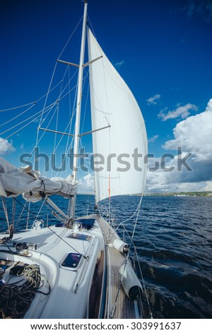 View from the board of a sailing yacht on the waters, sailing ships and the forest growing along the coast, as well as people's homes. sailing yacht floating in the wind on a beautiful sunny - stock photo