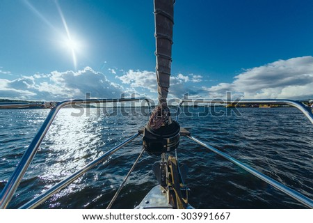 View from the board of a sailing yacht on the waters, sailing ships and the forest growing along the coast, as well as people's homes. - stock photo