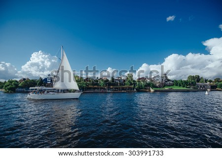View from the board of a sailing yacht on the waters, sailing ships and the forest growing along the coast, as well as people's homes. Sailing yacht sails past the dock at private homes. - stock photo
