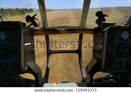 View from the cockpit of helicopter flying in low altitude above field - stock photo