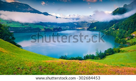 View from the hill on Lungerersee lake. Swiss village Lungern in the morning mist. Alps, Switzerland, Europe. - stock photo