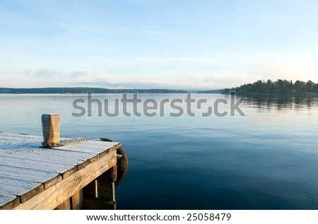 View from the jetty over a calm lake in the evening. - stock photo