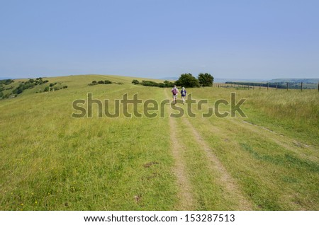 view from the south downs way footpath, sussex, england uk - fit senior couple walking on footpath - stock photo