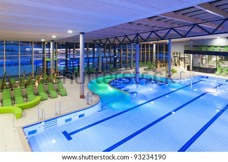 view from the top of a new swimming pool with green divans and lighted water - stock photo
