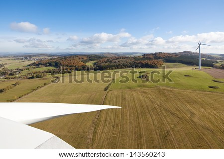 View from the top of a wind turbine over green fields - stock photo