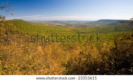 View from the top of Hawk Mountain, Pennsylvania, USA. Colorful fall foliage,  farmlands in the distance. - stock photo
