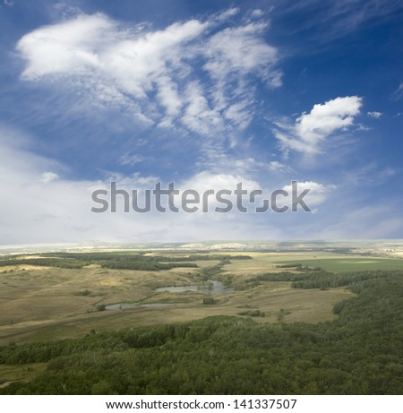 View from the top of the mountain. Blue sky and white clouds. Green field and summer forest. Beauty landscape - stock photo