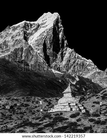 View from the village of Dingboche at ancient Buddhist stupa on the background of peak Tabuche - Everest region, Nepal, Himalayas (black and white) - stock photo