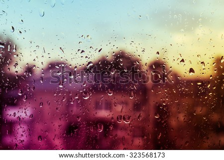 view from the window at the rain, thunder and lightning with drops on the glass - stock photo