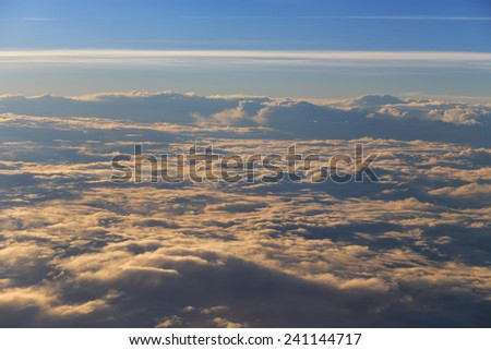 view from the window of an airplane flying above the clouds - stock photo