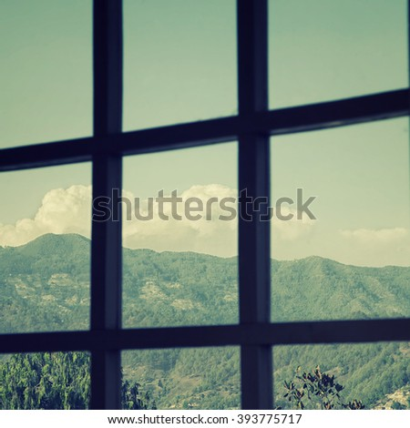 View from the window to mountains and sky with clouds - stock photo
