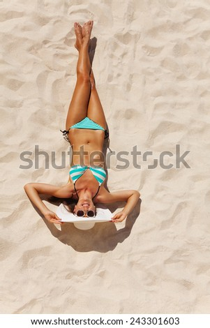 View from top of beautiful woman in bikini with white hat and sunglasses on beach sand in summer - stock photo