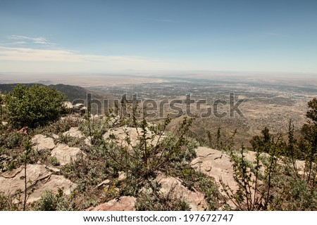 View from top of Sandia Mountains over Rio Grande Rift Valley, in state of New Mexico, USA/View from Sandia Mountaintop at Albuquerque, NM/Mountaintop view of distant desert valley and city below - stock photo