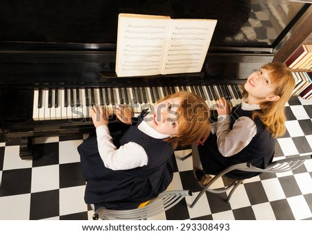 View from top of two girls in uniforms playing piano together with notes during lesson - stock photo
