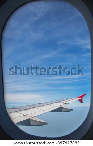 View from window of an airplane wing aircraft flying above the clouds in a blue sky. - stock photo