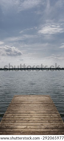 View from wooden landing plank at the lakeside on a sunny day - stock photo