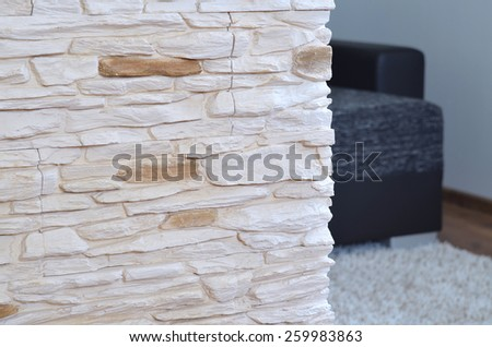 View into the living room through a wall tiled rough stone cladding - stock photo