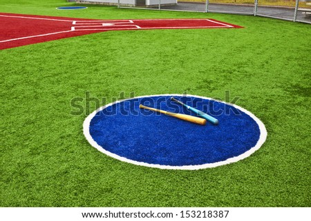 View is from a batter warm up circle looking towards home plate with artificial turf at a school softball field. The bright colors of the artificial turf are a high contrast to a normal playing field. - stock photo