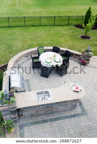 View looking down at a brick paved outdoor living area on an open-air patio with a gas BBQ and concrete kitchen counter alongside a dining table and chairs overlooking green lawns - stock photo