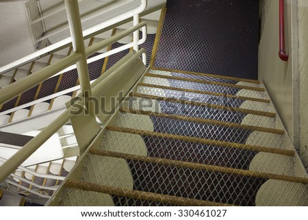 View looking down from above of an internal metal staircase - stock photo