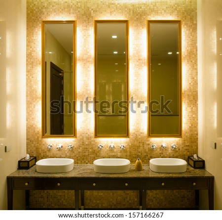 View Modern style interior design of a bathroom. Install bulb behind a mirror glass decorative gold picture frame and faucet and wash bowl on table - stock photo
